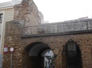 El arco de los Blanco, es la puerta  oriental de la muralla. Data del siglo XV.  Esta puerta con forma de arco apuntado  y bóveda de cañón, también fue llamada  Puerta de Tierra, por dar a la zona del  istmo. Junto al gran arco de acceso al  barrio del Pópulo, podemos apreciar  unos arcos apuntados que albergan un  pequeño corredor. Probablemente a  ambos lados del acceso al barrio se  ubicarían las carnicerías reales. Después  también fue conocida como Puerta de  Santa María, ya que daba al arrabal de  Santa María. En el siglo XVII, la familia  de comerciantes de Felipe Blanco pide  permiso para instalar sobre los arcos una capilla dedicada a la Virgen de los Remedios,  que fue finalizada hacia 1635, y de la cual actualmente no quedan vestigios. Actualmente  se conoce como arco de los Blanco, por la construcción que esta familia realizó en los  arcos.    Dejando atrás la calle de San Juan de Dios, nos encontramos en la Plaza de San  Juan de Dios, que alberga el Antiguo Hospital de San Juan de Dios y el Ayuntamiento.  Desde el siglo XVI hasta la actualidad la plaza ha recibido muchos nombres, tales como:  Corredera de las Águilas, Plaza de la Corredera, Plaza Real en 1644, Plaza de Armas,  Plaza de San Juan de Dios, Plaza de la Misericordia y Plaza de Isabel II. En esta plaza se  albergaron las casas de los gobernadores, la alhóndiga o almacén de trigo, el almacén de  armas, la cárcel Real y la pescadería. Al aumentar la población de la ciudad, en esta  plaza de ubicó el Mercado Mayor. También se utilizaba esta plaza para fiestas públicas,  autos sacramentales y corridas de toros.